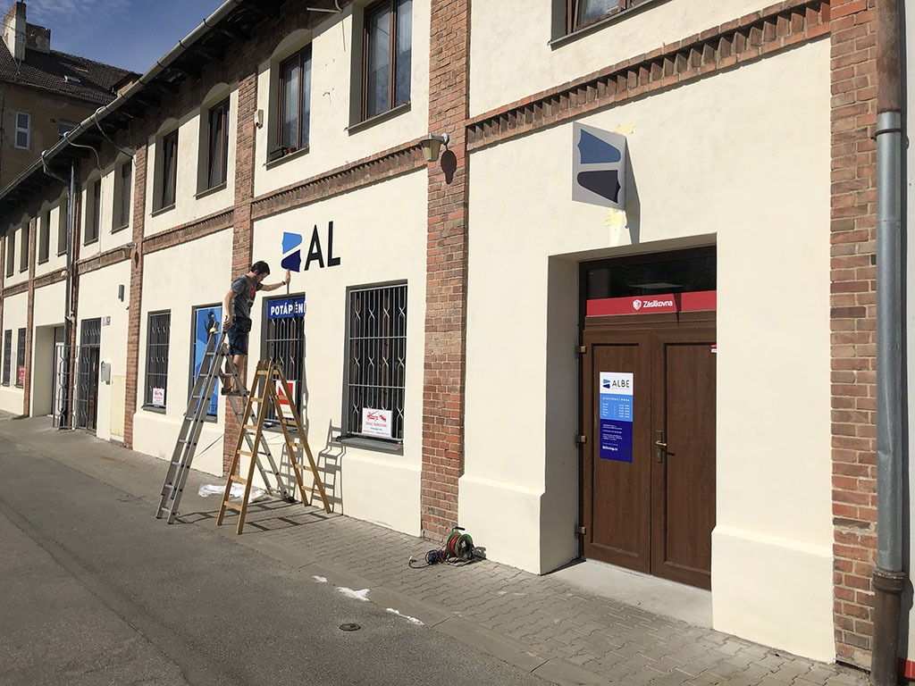 ALBE | Rekonstrukce fasády ALBE Brno - přidělávání loga na fasádu